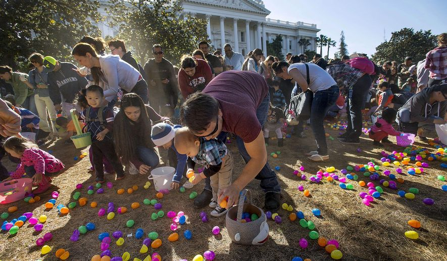 In this Saturday, April 4, 2015 photo, Rich Smith of south Sacramento, center, helps his son Charlie gather plastic Easter eggs during an Easter egg hunt event at the state Capitol in Sacramento, Calif. Organizers had ordered 510,000 plastic eggs in an attempt to break the current Guinness World Record of 501,000 eggs from a 2007 hunt in Florida. (AP Photo/The Sacramento Bee, Randall Benton) MAGS OUT; LOCAL TELEVISION OUT (KCRA3, KXTV10, KOVR13, KUVS19, KMAZ31, KTXL40); MANDATORY CREDIT