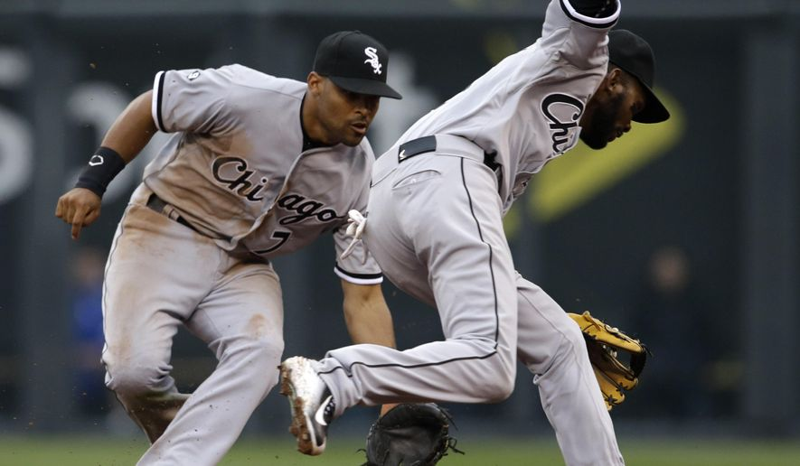 A ground ball hit by Kansas City Royals' Alex Gordon gets through Chicago White Sox infielders Alexei Ramirez, right, and Micah Johnson, left, during the seventh inning of a baseball game at Kauffman Stadium in Kansas City, Mo., Monday, April 6, 2015. Two runs scored on the play. (AP Photo/Orlin Wagner)