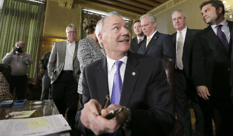 Arkansas Gov. Asa Hutchinson hands out pens to legislators after signing bills at the Arkansas state Capitol in Little Rock, Ark., Monday, April 6, 2015. Hutchinson signed into law three bills aimed at overhauling the state's workforce education programs. (AP Photo/Danny Johnston)
