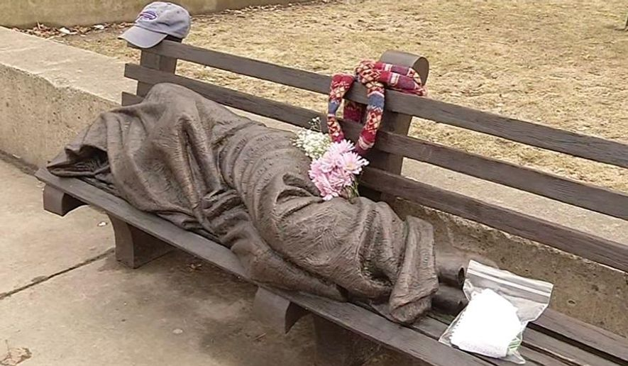 An April 3, 2015 image from video shows a work by Canadian sculptor Timothy Schmalz, a blanket-shrouded Jesus identifiable only by the crucifixion wounds on his feet, outside St. Paul's Episcopal Cathedral in Buffalo, NY. The unveiling of the statue on March 31 has prompted people to leave money, food and other items at the bronze sculpture. The offerings are apparently meant for Buffalo's homeless. (AP Photo/courtesy of WIVB-TV) BUFFALO OUT