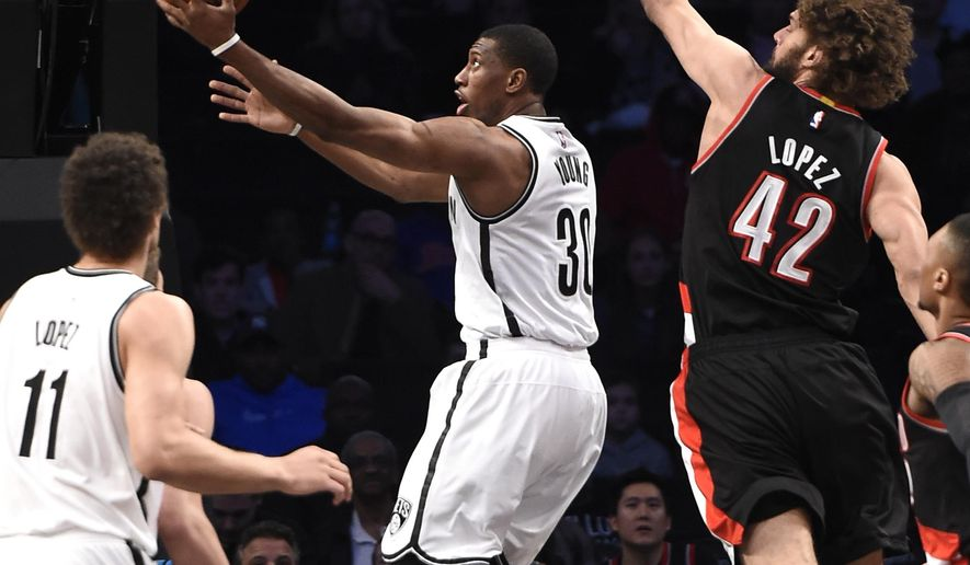Brooklyn Nets forward Thaddeus Young (30) leaps for a basket past Portland Trail Blazers center Robin Lopez (42) as  Nets center Brook Lopez (11) awaits the rebound in the first half of an NBA basketball game on Monday, April 6, 2015, in New York. (AP Photo/Kathy Kmonicek)