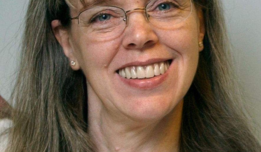 FILE -  In this 2003, file photo, former Associated Press photo editor Madge Stager smiles for a picture, in New York. Stager, 61, who retired in 2009 after 37 years with The AP, died at at a New York hospital on Saturday, April 4, 2015, after a brief illness. As a New York-based photo editor, Stager was a familiar, straight-talking voice to journalists around the world, assisting them in chronicling such stories as the wars in Iraq and Afghanistan, numerous Olympic Games and the Sept. 11 terror attacks. (AP Photo/Richard Drew, File)