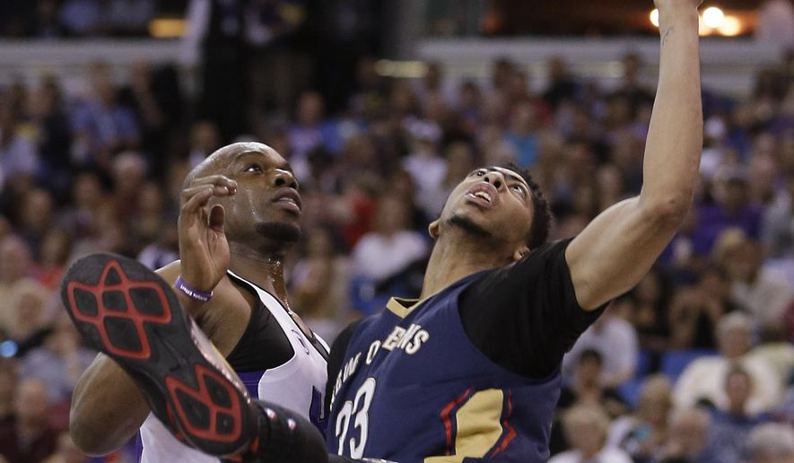 Sacramento Kings forward Carl Landry, left, and New Orleans Pelicans forward Anthony Davis go for a rebound during the second half of an NBA basketball game in Sacramento, Calif., Friday, April 3, 2015. The Pelicans won 101-95. (AP Photo/Rich Pedroncelli)