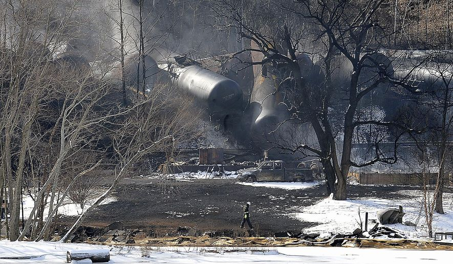 FILE - This Feb. 17, 2015 file photo shows a crew member walking near the scene of a train derailment near Mount Carbon, W.Va. Tank cars carrying oil or ethanol by rail urgently need to be retrofitted to make them more fire-resistant after a spate of explosive accidents in recent months revealed the shortcomings of industry-backed safety standards, U.S. officials said Monday, April 6, 2015. (AP Photo/Chris Tilley, File)