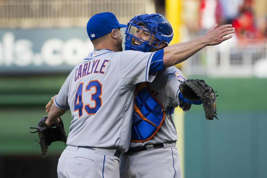 New York Mets relief pitcher Buddy Carlyle, left, celebrates with catcher Travis d'Arnaud after earning a save in a 3-1 opening day victory over the Washington Nationals at Nationals Park on Monday, April 6, 2015, in Washington. (AP Photo/Evan Vucci)