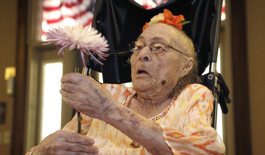 FILE - In this July 3, 2014, file photo, Gertrude Weaver holds a flower given to her a day before her 116th birthday at Silver Oaks Health and Rehabilitation Center in Camden, Ark. Just days after becoming the world's oldest documented person, 116-year-old Gertrude Weaver died Monday, April 6, 2015, in Arkansas. (AP Photo/Danny Johnston, File)