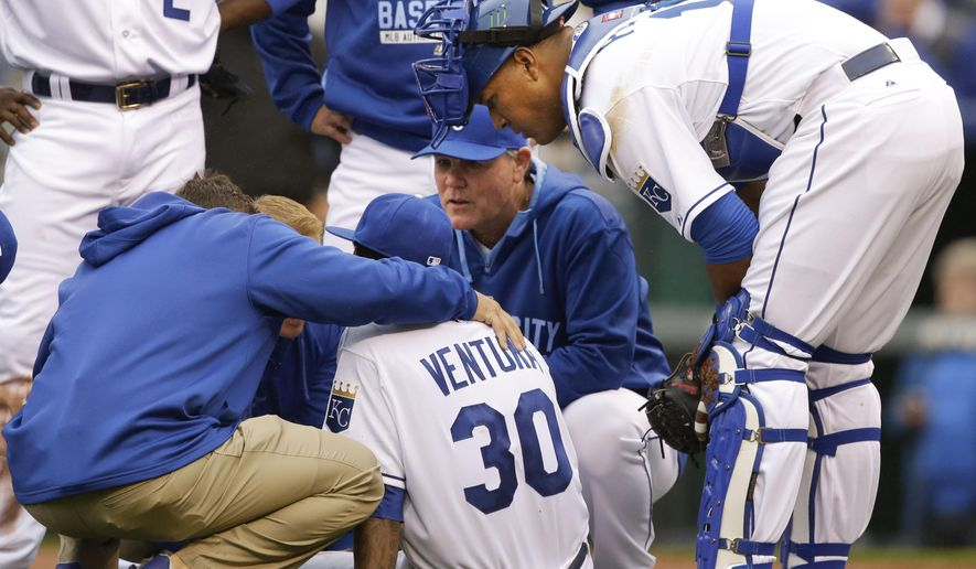 Kansas City Royals manager Ned Yost, back, and catcher Salvador Perez, right,   check on starting pitcher Yordano Ventura (30)    after an injury during the seventh inning of a baseball game against the Chicago White Sox at Kauffman Stadium in Kansas City, Mo., Monday, April 6, 2015. (AP Photo/Orlin Wagner)