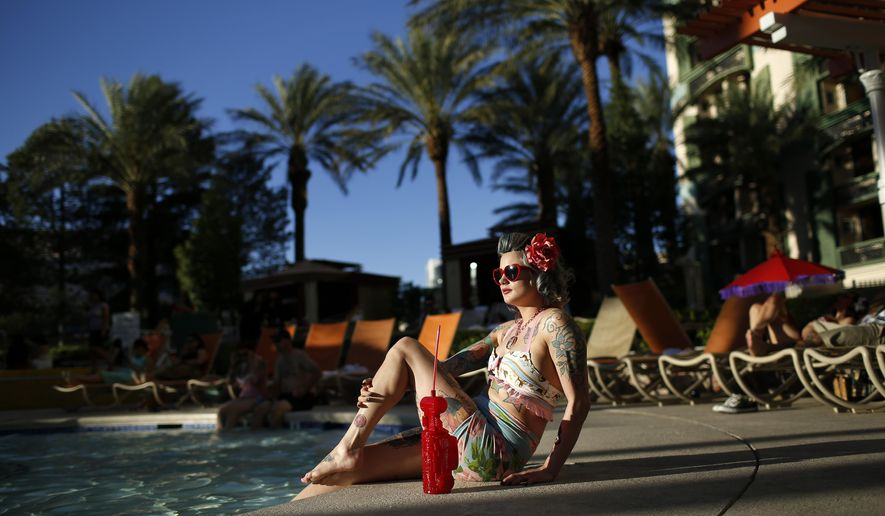 In this April 4, 2015, photo, a woman who goes by Martha War sits by the pool during the Viva Las Vegas Rockabilly Weekend in Las Vegas. Thousands of rockabilly fans attended the 18-year-old event. (AP Photo/John Locher)