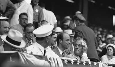 President Franklin D. Roosevelt looks at his son, James, between action in the All-Star Game in Washington on July 7, 1937. Except for the heat, it was an ideal day for the game and more than 30,000 fans jammed Griffith Stadium to see baseball's headliners play in the sport's tip-top attraction. (AP Photo)