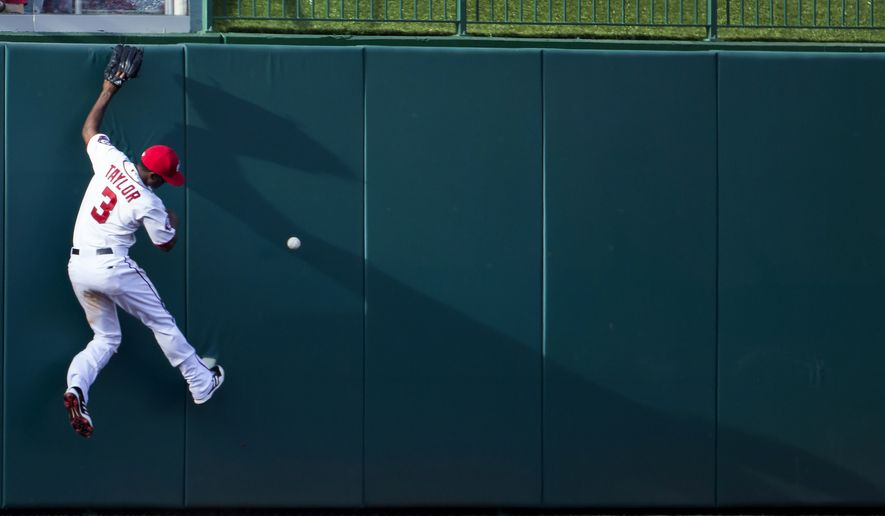 Washington Nationals center fielder Michael Taylor tries to catch an RBI triple hit by New York Mets Travis d'Arnaud during the seventh inning of an opening day baseball game at Nationals Park on Monday, April 6, 2015, in Washington. The Mets defeated the Nationals 3-1. (AP Photo/Evan Vucci)