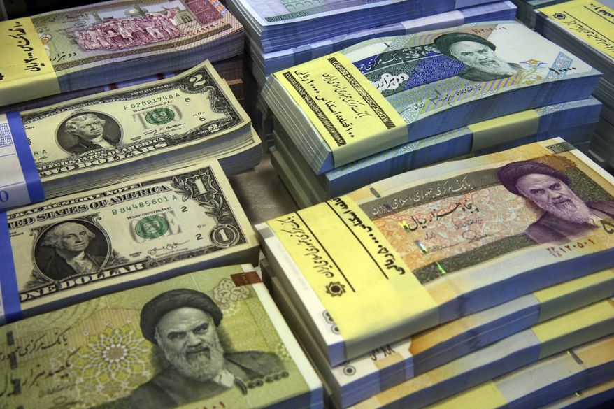 In this Saturday, April 4, 2015 photo, Iranian and U.S. banknotes are on display at a currency exchange shop in downtown Tehran, Iran. Should Iran reach a final nuclear accord with world powers that loosens sanctions, the economic opening could give moderates a major boost ahead of crucial parliamentary elections next February. (AP Photo/Vahid Salemi)