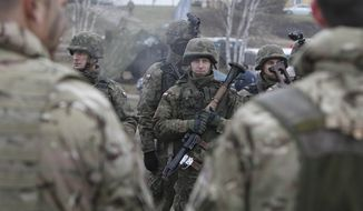 In this Nov. 21, 2014, file photo, Polish and British troops take part in a joint military exercise in Swietoszow, Poland, with more than 1,000 British troops participating. Across many nations of eastern Europe ordinary people are heeding a call to receive military training to learn what to do in case of war, and backed by NATO forces on a mission to reassure citizens that they're safe from Russian aggression. (AP Photo/Czarek Sokolowski, File)