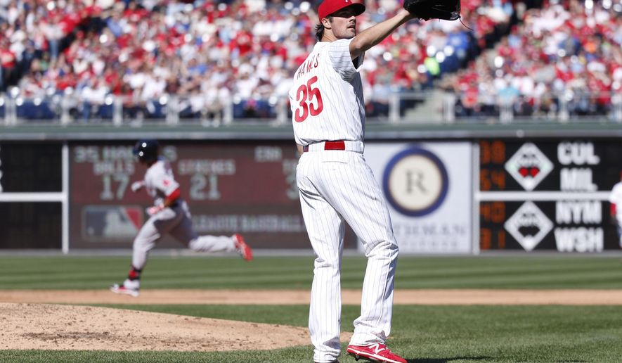Philadelphia Phillies starting pitcher Cole Hamels, right, looks for a new ball after Boston Red Sox Mookie Betts, left, hit a solo home run during the third inning of an opening day baseball game, Monday, April 6, 2015, in Philadelphia. (AP Photo/Chris Szagola)
