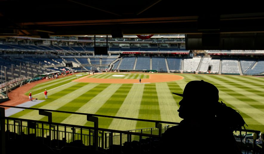 A stadium worker sits above the field before a baseball game between the Washington Nationals and the New York Mets on opening day at Nationals Park, Monday, April 6, 2015, in Washington. (AP Photo/Andrew Harnik)