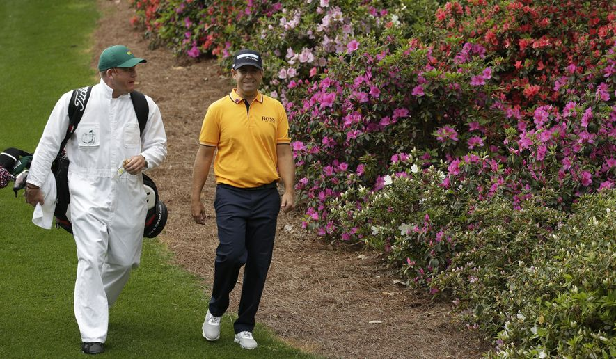 Erik Compton walks with his caddie down the sixth fairway during a practice round for the Masters golf tournament Monday, April 6, 2015, in Augusta, Ga. (AP Photo/Charlie Riedel)