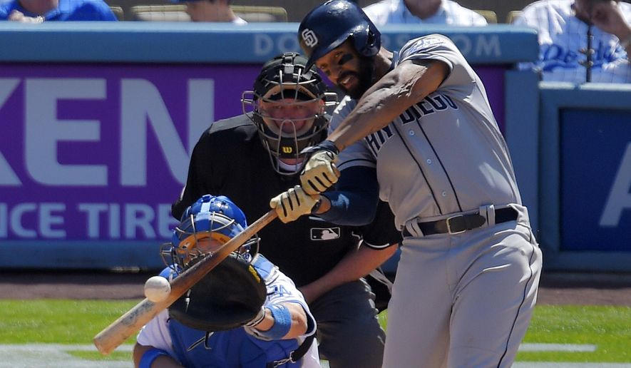 San Diego Padres' Matt Kemp, right, hits an RBI double while Los Angeles Dodgers catcher A.J. Ellis, left, and home plate umpire Brian Gorman watch during the fifth inning of an opening day baseball game, Monday, April 6, 2015, in Los Angeles. (AP Photo/Mark J. Terrill)