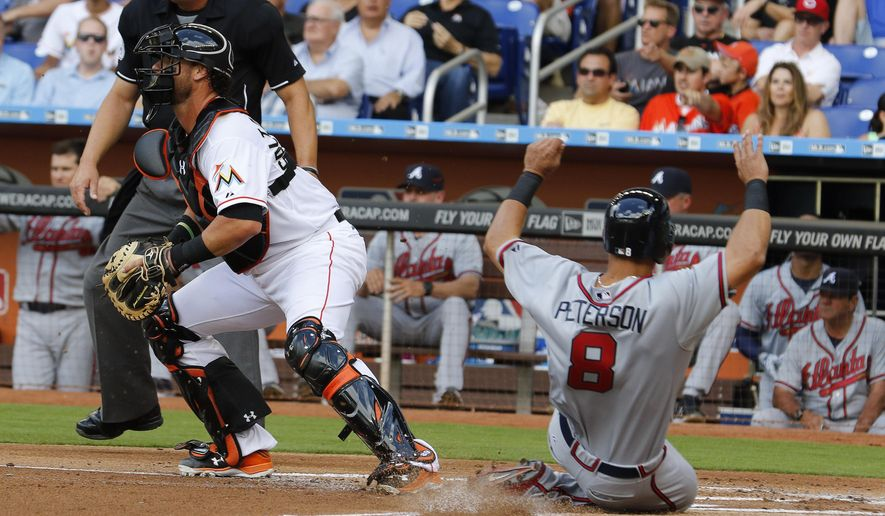 Atlanta Braves baserunner Jace Peterson  slides to score on a single by teammate Nick Markakis in the first inning as Miami Marlins catcher Jarrod Saltalamacchia waits for the late throw during their opening day baseball game in Miami, Monday, April 6, 2015. (AP Photo/Joe Skipper)