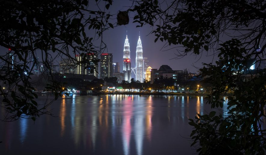 Malaysia's landmark Petronas Twin Towers illuminates the night skyline in Kuala Lumpur, Malaysia, Monday, April 6, 2015. Malaysia's police chief said Monday that 17 suspected militants were detained Sunday for allegedly plotting to carry out terrorist acts in the country's largest city. Inspector General of Police Khalid Abu Bakar tweeted that two of them had just returned from Syria. (AP Photo/Joshua Paul)