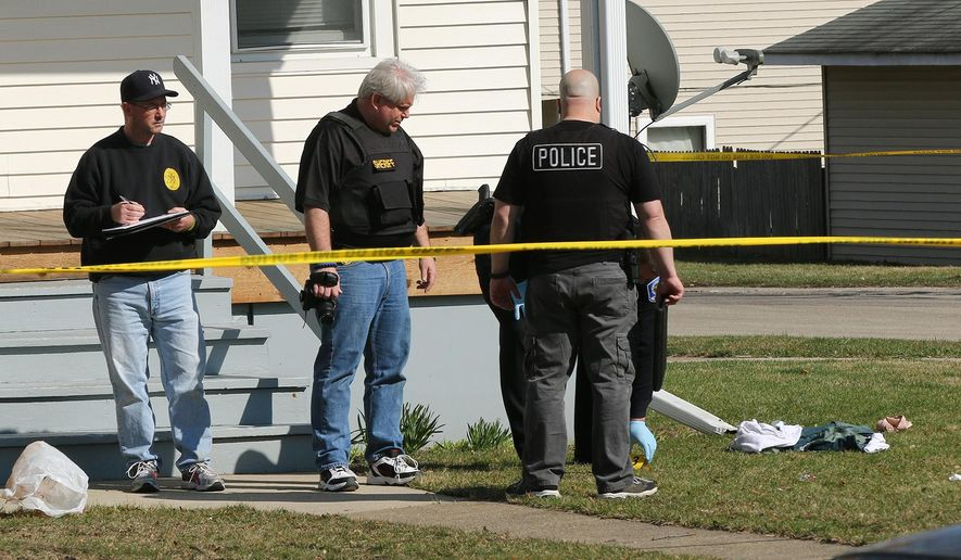 Investigators look over the scene following a police involved shooting in Zion, Ill., on Saturday, April 4, 2015, after a Zion Police officer was involved in a fatal shooting. An autopsy has revealed that a teenager who was killed by police in Illinois over the weekend was shot twice in the back. (AP Photo/The Chicago Tribune, Joe Shuman)
