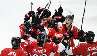 Ottawa Senators' Mark Stone (61) is surrounded by his teammates after scoring the game winning goal against the Pittsburgh Penguins during overtime of an NHL hockey game in Ottawa, Ontario, on Tuesday, April 7, 2015. The Senators defeated the Penguins 4-3. (AP Photo/The Canadian Press, Justin Tang)