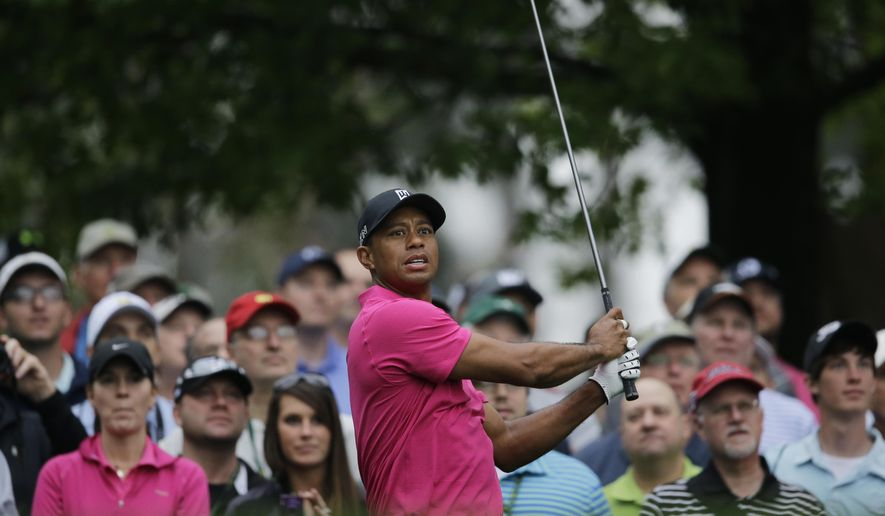 Tiger Woods watches his tee shot on the fourth hole during a practice round for the Masters golf tournament Tuesday, April 7, 2015, in Augusta, Ga. (AP Photo/Matt Slocum)