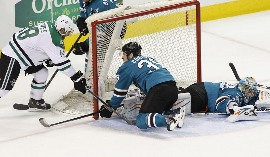 Dallas Stars' Patrick Eaves, left, scores a goal against the San Jose Sharks during the first period of an NHL hockey game, Monday, April 6, 2015, in San Jose, Calif. At center is Sharks' Logan Couture and at right is goalie Alex Stalock. (AP Photo/George Nikitin)
