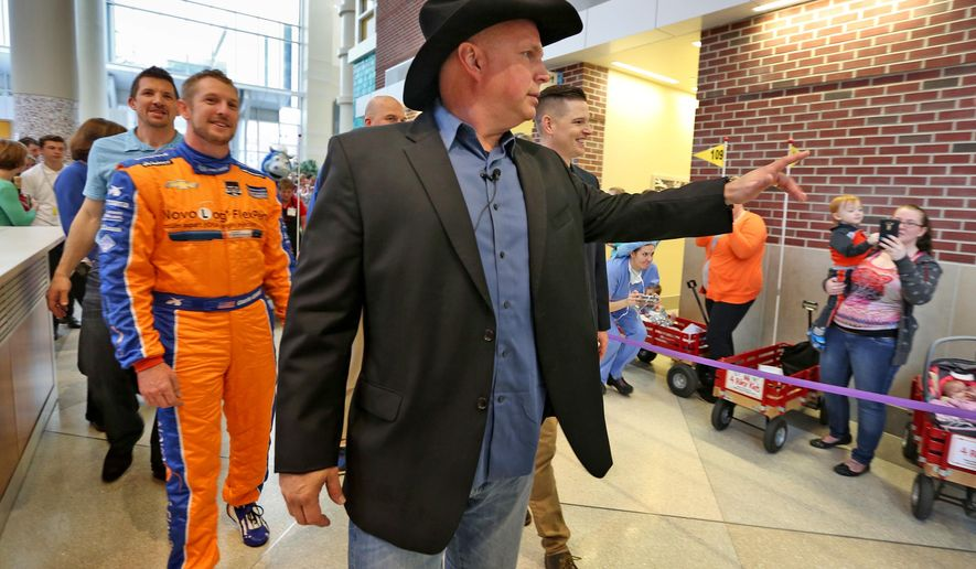 Country music star Garth Brooks, front, leads other celebrities, including former Colts player Dallas Clark, and IndyCar driver Charlie Kimball on a parade through the halls of Riley Hospital for Children, Tuesday, April 7, 2015, in Indianapolis. Brooks attended the Child Life Zone ribbon cutting at the hospital Tuesday, which was funded through the Teammates for Kids foundation, which Brooks co-founded in 1999. (AP Photo/The Indianapolis Star, Kelly Wilkinson)  NO SALES
