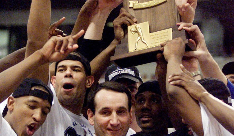 FILE - In this April 2, 2001, file photo, Duke coach Mike Krzyzewski and his Blue Devils hoist the championship trophy after beating Arizona 82-72 in the championship game of the Final Four in Minneapolis. His national championships came in 1991, 1992, 2001, 2010 and now 2015.  (AP Photo/Bob Jordan, File)