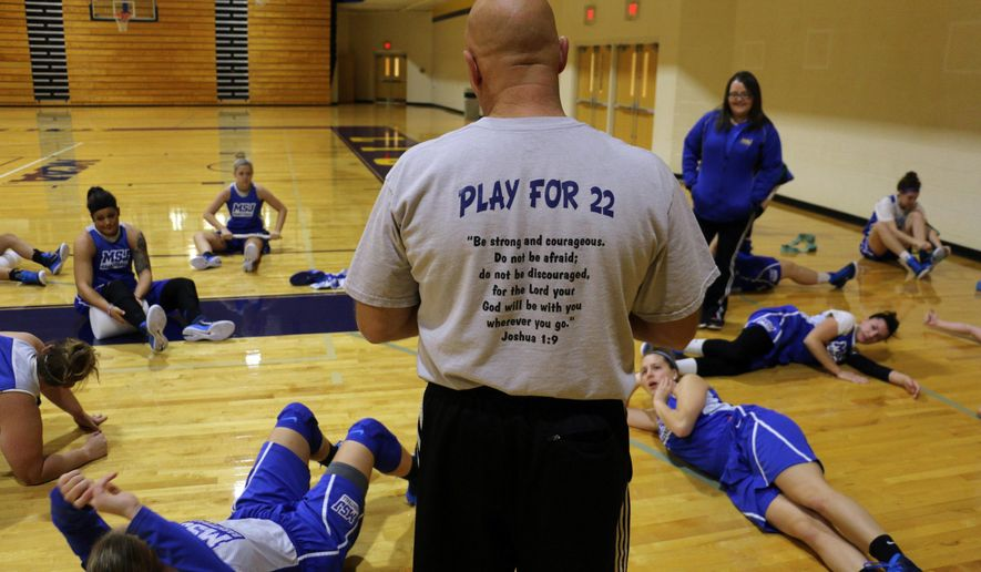 FILE - In this Oct. 23, 2014, file photo, coach Dan Benjamin wears a T-shirt with Lauren Hill's number as he runs the practice for the NCAA college basketball team at Mount St. Joseph University in Cincinnati. Lauren Hill is using her limited energy and her final days to try to inspire people and raise money for research into the cancer that is taking her life. (AP Photo/Tom Uhlman, File)