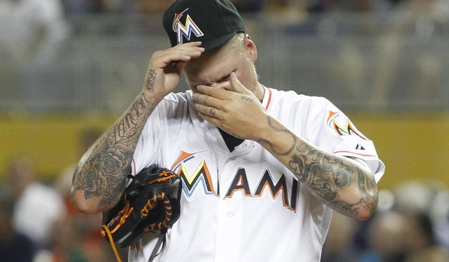 Miami Marlins starting pitcher Mat Latos reacts in the first inning of play against the Atlanta Braves   during their baseball game in Miami, Tuesday, April 7, 2015. Latos was taken from the game in the first inning. (AP Photo/Joe Skipper)