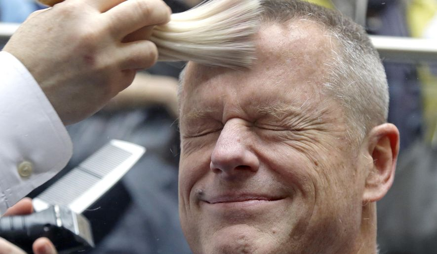 Massachusetts Gov. Charlie Baker reacts as he gets a buzz cut during a fundraising drive at Granite Telecommunications in Quincy, Mass., Tuesday, April 7, 2015 in support of the Dana-Farber Cancer Institute. Baker joined more than 500 company employees who shaved their heads to raise over $3.5 million for cancer research. (AP Photo/Elise Amendola)