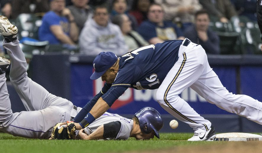 Milwaukee Brewers' Aramis Ramirez can not make the catch at third as Colorado Rockies' Justin Morneau dives back to the base during the seventh inning of a baseball game Tuesday, April 7, 2015, in Milwaukee. (AP Photo/Tom Lynn)