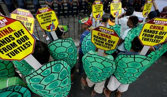 Police face off with protesters dressed as green sea turtles during a rally last year in front of the Chinese Consulate at the financial district of Makati city to protest poaching in the South China Sea. Beijing's accelerated land reclamation in recent years has only escalated the friction among claimants. In particular, China's expansion in Johnson and Gaven reefs threatens to wreck rich fishing grounds and valuable coral reefs in the archipelago. (Associated Press)