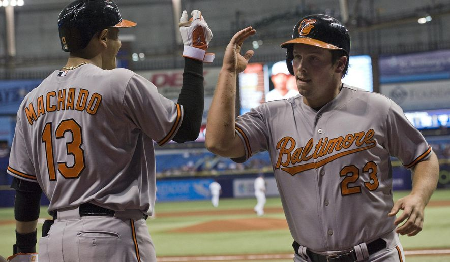 Baltimore Orioles' Manny Machado (13) congratulates Travis Snider (23) after Snider scored on Adam Jones' two-run double during the first inning of a baseball game against the Tampa Bay Rays, Tuesday, April 7, 2015 in St. Petersburg, Fla. (AP Photo/Steve Nesius)