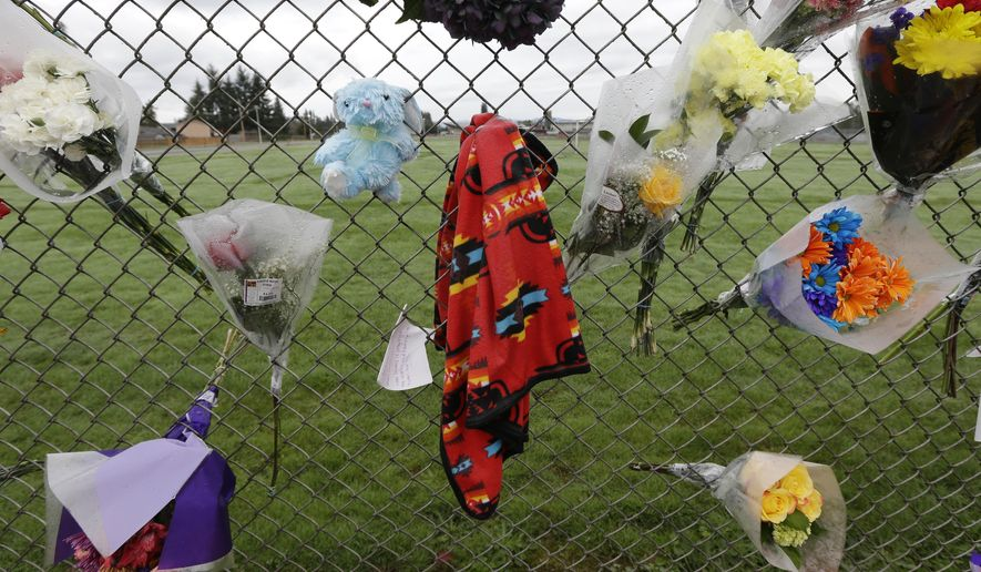 FILE - In this Oct. 27, 2014, file photo, an Indian-style blanket hangs along with flowers, notes, and a stuffed animal at a growing memorial at Marysville Pilchuck High School in Marysville, Wash., where Jaylen R. Fryberg, 15, a student at the school and a member of the Tulalip Tribes, opened fire Oct. 24, 2014, in the school cafeteria. A glitch in the reporting system between tribal courts and criminal databases allowed Fryberg's father to purchase the handgun that was later used by his son in the fatal shooting. (AP Photo/Ted S. Warren, File)