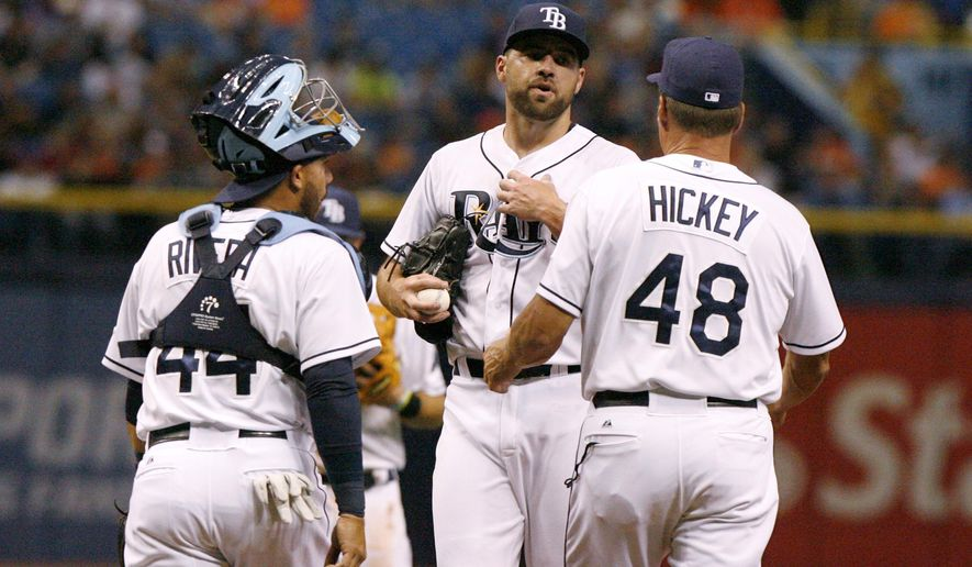 Tampa Bay Rays catcher Rene Rivera and pitching coach Jim Hickey (48) approach the mound to talk with starting pitcher Nathan Karns during a baseball game against the Baltimore Orioles on Tuesday, April 7, 2015, in St. Petersburg, Fla. (AP Photo/Tampa Bay Times, Douglas R. Clifford)