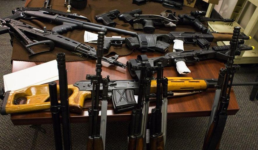 Weapons lay displayed on a table before a news conference about how the weapons, as well as ammunition, were discovered in the home of two local school bus drivers thought to be part of the Michigan Militia on Tuesday, April 7, 2015 at the Genesee County Sheriff's Department in Flint, Mich. The guns were seized after investigators claimed they were purchased with money embezzled by the couple. (AP Photo/The Flint Journal, Brittany Greeson)
