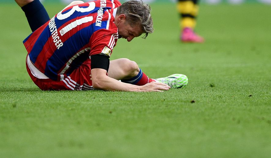 In this April 4, 2015 picture Munich's Bastian Schweinsteiger kneels on the ground while touching his left ankle during the German Bundesliga soccer match between Borussia Dortmund and Bayern Munich  in Dortmund, Germany. Bastian Schweinsteiger could miss the German Cup quarterfinal against Bayer Leverkusen on Wednesday because of an ankle injury. (AP Photo/dpa, Jonas Guettler)