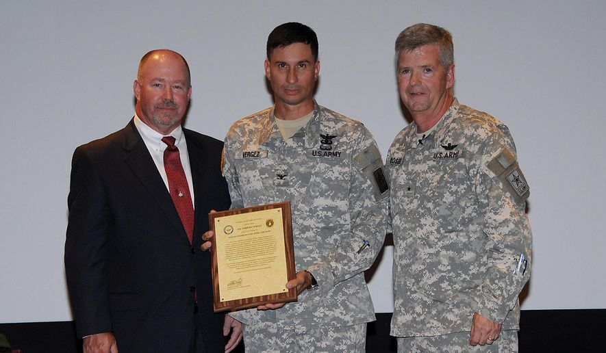 In this 2010 photo provided by the U.S. Army, Col. Norbert Vergez, center, receives his charter to manage the Project Office for Non-Standard Rotary Wing Aircraft (NSRWA) from the Program Executive Officer for Aviation, now Maj. Gen. William Crosby, right, and Randy Harkins, former deputy project manager NSRWA. On Tuesday, April 7, 2015, Vergez pleaded guilty to negotiating his post-military employment with a helicopter company that did business with the Defense Department office he managed. (AP Photo/U.S. Army)