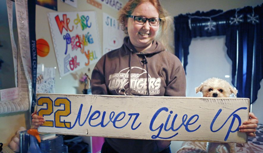 FILE - In this Dec. 8, 2014, file photo, Lauren Hill holds a sign made for her, which she keeps in her room in Cincinnati, along with many other messages and gifts of support. Hill is using her limited energy and her final days to try to inspire people and raise money for research into the cancer that is taking her life. (AP Photo/The Enquirer, Carrie Cochran, File)  NO SALES