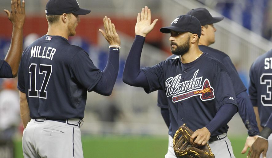 Atlanta Braves right fielder Nick Markakis, right, celebrates the Braves' 12-2  win over the Miami Marlins with pitcher Shelby Miller following their baseball game in Miami, Tuesday, April 7, 2015. (AP Photo/Joe Skipper)