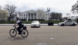 A Secret Service rides his bike on Pennsylvania Avenue outside the White House in Washington, Tuesday, April 7, 2015. The White House, State Department, and Capitol were all affected by reports of widespread power outages across Washington and its suburbs Tuesday afternoon. (Associated Press)