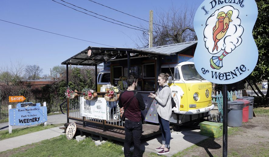 In this April 4, 2015, photo, customers visit the I Dream of Weenie hot dog stand, housed in a Volkswagen Microbus, in the East Nashville area of Nashville, Tenn. East Nashville houses an eclectic collection of restaurants, bars, coffee shops, bakeries and stores, mixed into a residential area of 1950s and 1960s homes. (AP Photo/Mark Humphrey)