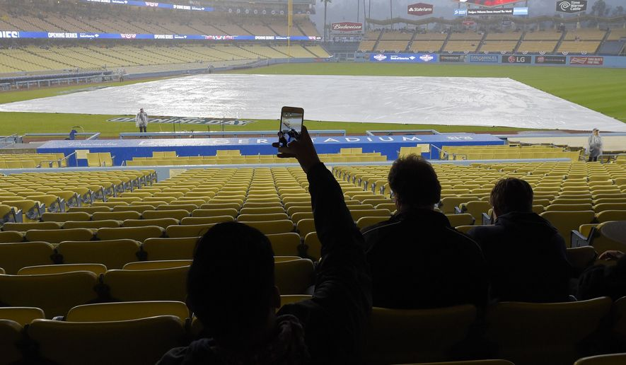 A fan takes a picture during a rain delay prior to a baseball game between the Los Angeles Dodgers and the San Diego Padres, Tuesday, April 7, 2015, in Los Angeles. (AP Photo/Mark J. Terrill)
