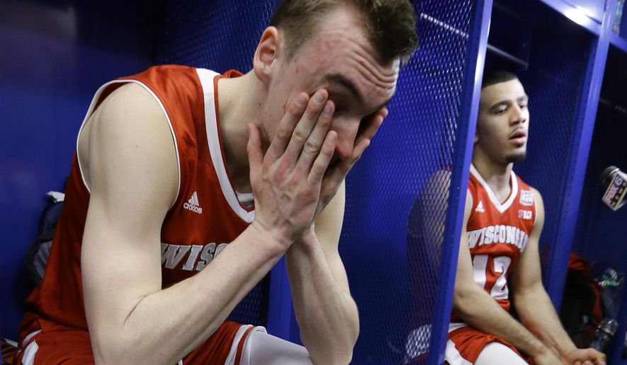 Wisconsin's Sam Dekker, left, and Traevon Jackson sit in the locker room after their team's 68-63 loss to Duke in the NCAA Final Four college basketball tournament championship game Monday, April 6, 2015, in Indianapolis. (AP Photo/Michael Conroy)