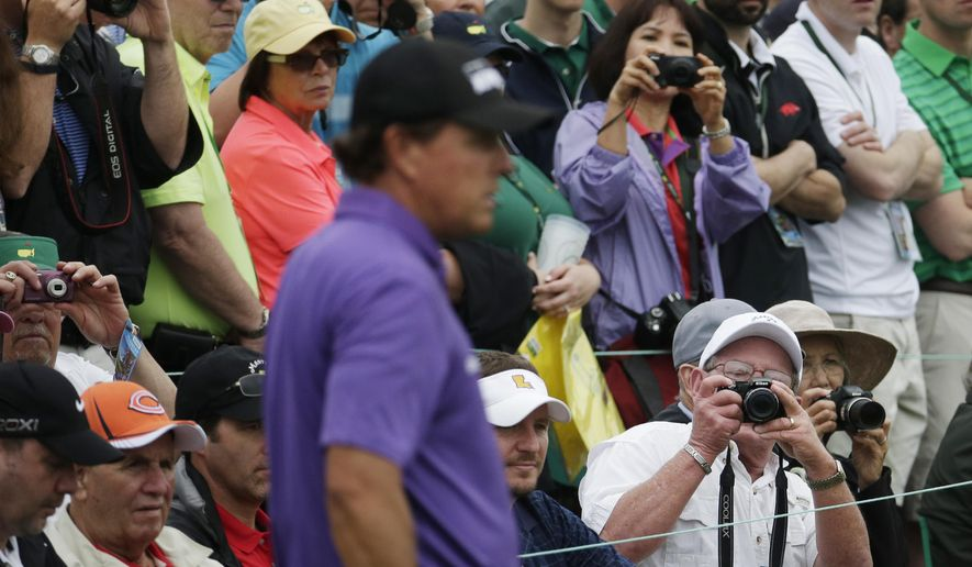 Spectators take photos of Phil Mickelson during a practice round for the Masters golf tournament Tuesday, April 7, 2015, in Augusta, Ga. (AP Photo/Charlie Riedel)