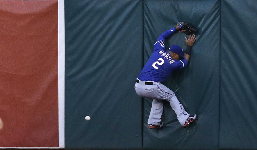 Texas Rangers center fielder Leonys Martin leaps up on the outfield wall trying to catch a fly ball hit by the Oakland Athletics' Sam Fuld in the first inning of their opening day baseball game Monday, April 6, 2015, in Oakland, Calif. Fuld tripled on the play. (AP Photo/Eric Risberg)