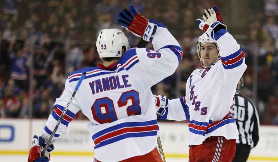 New York Rangers defenseman Ryan McDonagh, right, celebrates with teammate Keith Yandle after McDonaugh scored a goal against the New Jersey Devils during the first period of an NHL hockey game, Tuesday, April 7, 2015 in Newark, N.J. (AP Photo/Julio Cortez)