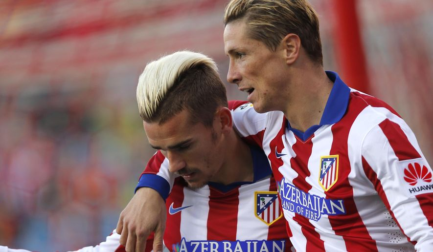 Antoine Griezmann from France, left, celebrates with Fernando Torres after scoring a goal during a Spanish La Liga soccer match between Atletico de Madrid and Real Sociedad at the Vicente Calderon stadium in Madrid, Spain, Tuesday, April 7, 2015. (AP Photo/Daniel Ochoa de Olza)