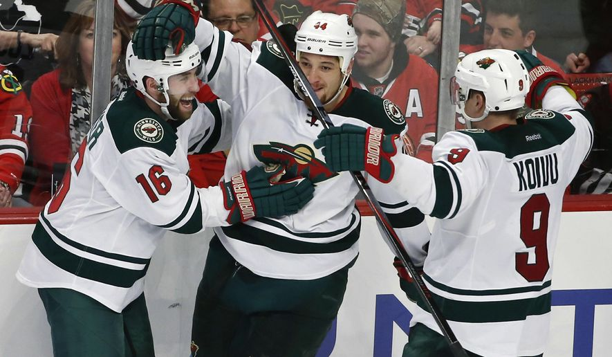 Minnesota Wild left wing Jason Zucker (16) celebrates with teammates right wing Chris Stewart (44) and center Mikko Koivu (9) a goal against the Chicago Blackhawks during the third period of an NHL hockey game Tuesday, April 7, 2015, in Chicago. The Wild won 2-1. (AP Photo/Kamil Krzaczynski)
